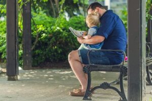 Man reading to his daughter